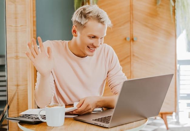 Счастливый деловой человек, сидя в кафетерии с ноутбуком и смартфоном. бизнесмен текстовых сообщений на смартфоне, сидя в кафе, работая и проверяя электронную почту на компьютере