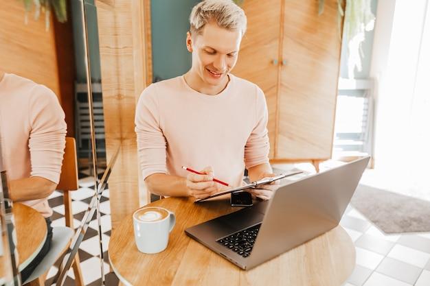 Счастливый деловой человек сидит в кафетерии с ноутбуком и смартфоном, отправляя текстовые сообщения на смартфон