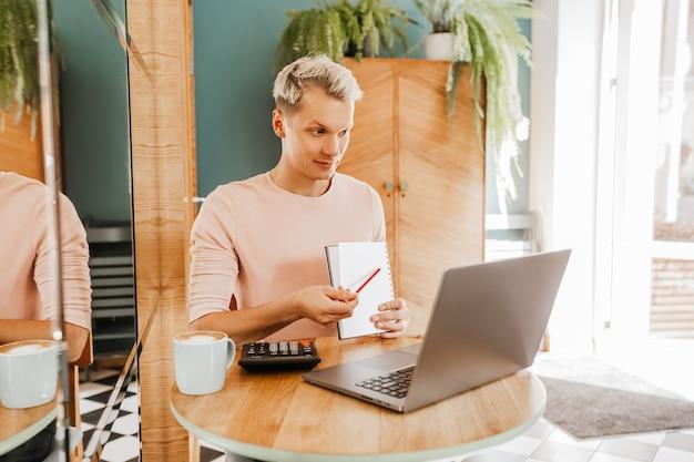 Счастливый деловой человек, сидя в кафетерии с ноутбуком и смартфоном