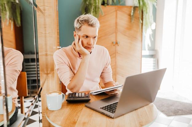 Счастливый деловой человек, сидя в кафетерии с ноутбуком и смартфоном.