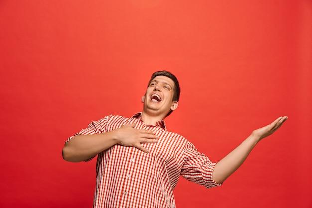 幸せなビジネスの男性が立っていると赤い壁に笑みを浮かべてします。