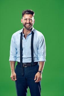 緑のスタジオに孤立して立って笑顔で幸せなビジネスマン。