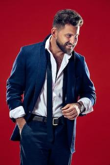 幸せなビジネスの男性に立って、赤いスタジオで分離された笑顔