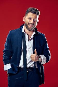 Uomo d'affari felice in piedi e sorridente su sfondo rosso.