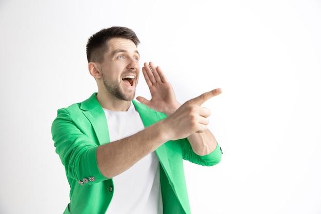 행복 한 비즈니스 사람 서, 웃 고 회색 공간에 고립 된 왼쪽을 가리키는. 아름다운 남성 반장 초상화. 젊은 만족 남자 무료 사진