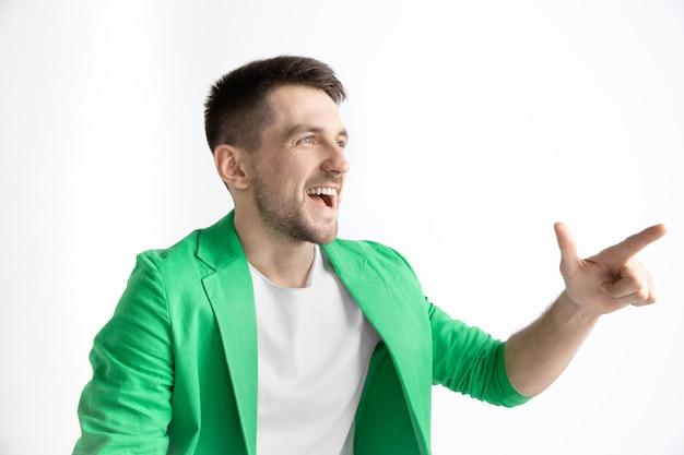 행복 한 비즈니스 사람 서, 웃 고 회색 스튜디오 배경에 고립 된 왼쪽을 가리키는. 아름다운 남성 반장 초상화. 젊은 만족 남자. 인간의 감정, 표정 개념.
