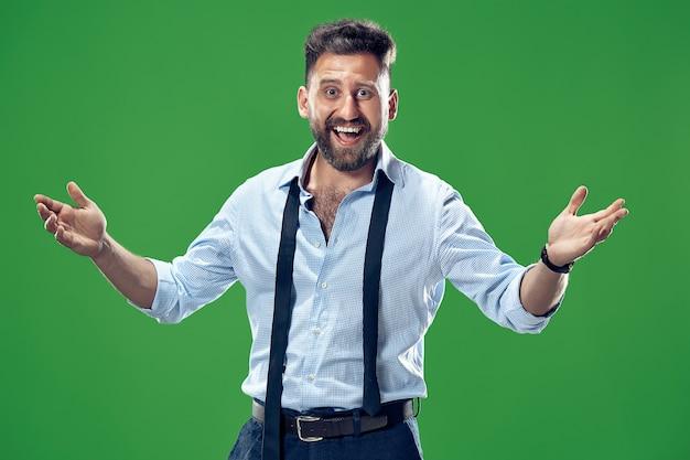 Uomo d'affari felice in piedi e sorridente isolato sulla parete verde dello studio