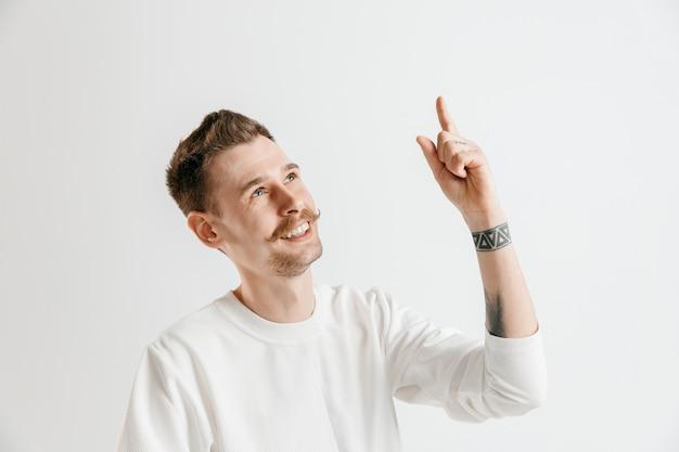 서, 웃 고 회색 스튜디오 배경에 고립 행복 비즈니스 사람. 아름다운 남성 반장 초상화. 젊은 만족 남자 가리키는. 인간의 감정, 표정 개념.