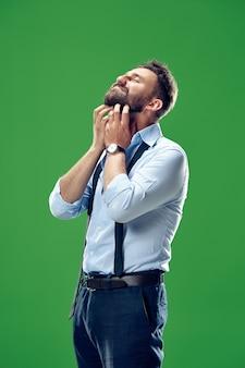 서, 웃 고 유행 녹색 스튜디오 배경에 고립 행복 비즈니스 사람. 아름다운 남성 반장 초상화. 젊은 만족 남자. 인간의 감정, 표정 개념. 전면보기.