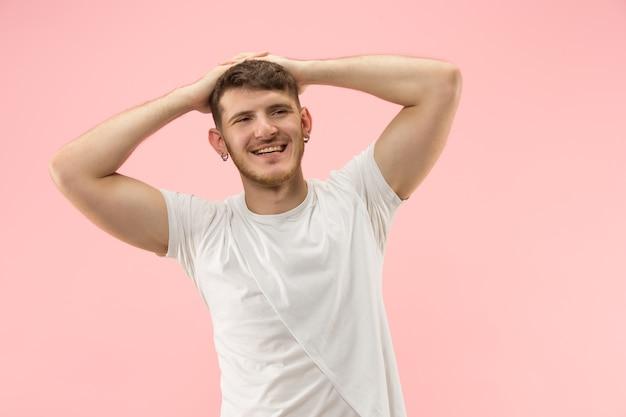 Счастливый деловой человек, стоящий, улыбаясь, изолирован на модной розовой студии