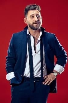 Uomo d'affari felice in piedi e sorridente isolato su sfondo rosso studio.