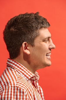 Uomo d'affari felice in piedi e sorridente isolato su studio rosso.