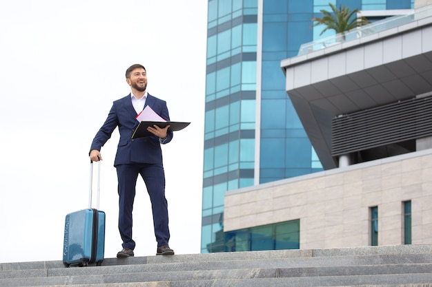 Happy business man stands with travel suitcase on the steps against office building with business project documents in hands