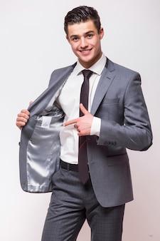 白い壁に孤立して立っている灰色のスーツを着て幸せなビジネス男