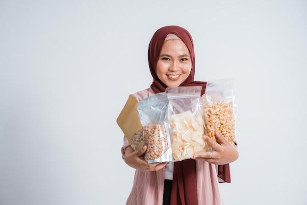 幸せなビジネスイスラム教徒の女性の肖像画は、小さな袋にスナックをもたらします