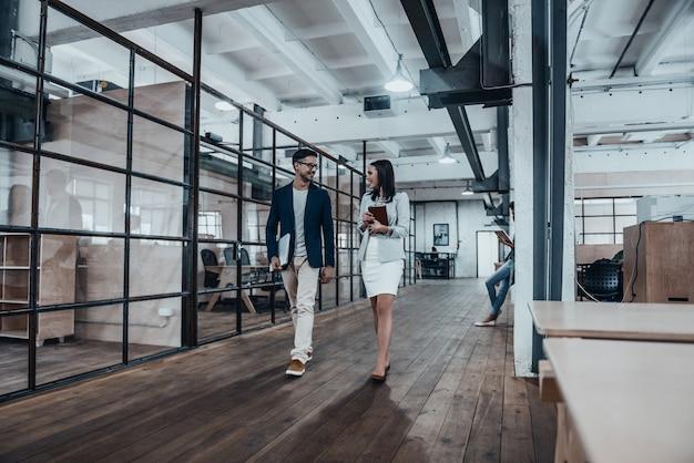 Счастливые деловые партнеры. в полный рост двое молодых коллег в элегантной повседневной одежде
