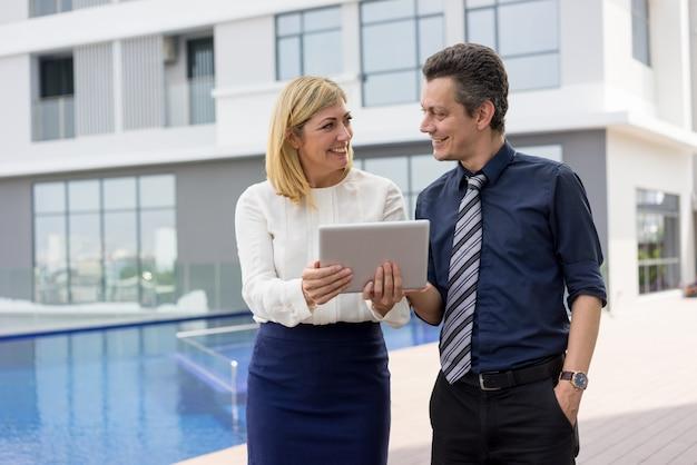 Счастливые деловые партнеры, читающие новости на планшетном компьютере на открытом воздухе.
