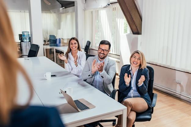 幸せなビジネスマンのリーダーや同僚に拍手を送る。視点。