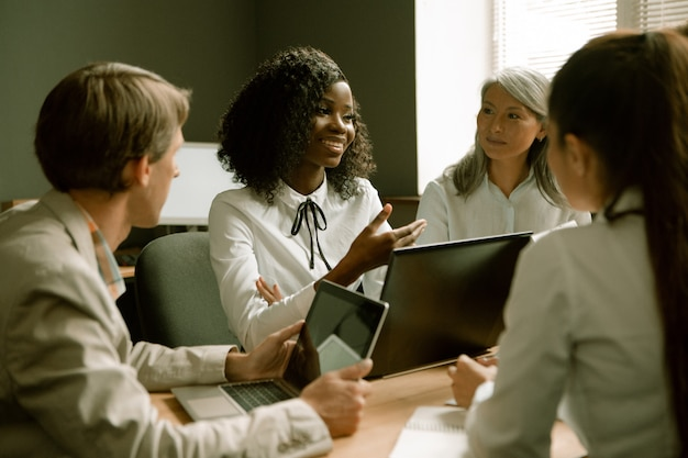 Счастливые деловые люди болтают на деловой встрече в офисе