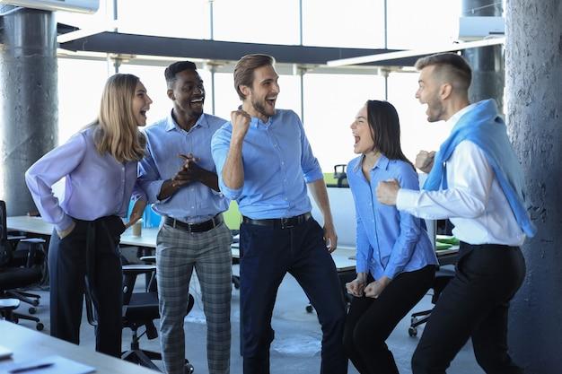 幸せなビジネスマンはオフィスで笑います。成功したチームの同僚は冗談を言って、仕事で一緒に楽しんでいます。
