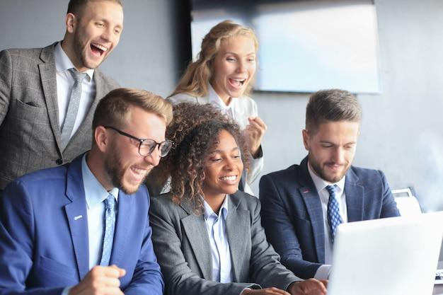 幸せなビジネスマンは、オフィスのラップトップの近くで笑います。成功したチームの同僚は冗談を言って、仕事で一緒に楽しんでいます。
