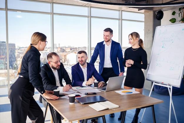 ノートパソコンのプレゼンテーション、仕事での成功、現代のオフィスに座って見て幸せなビジネスの人々。成功したオンライン交渉。ビジネスマンは知識を共有します