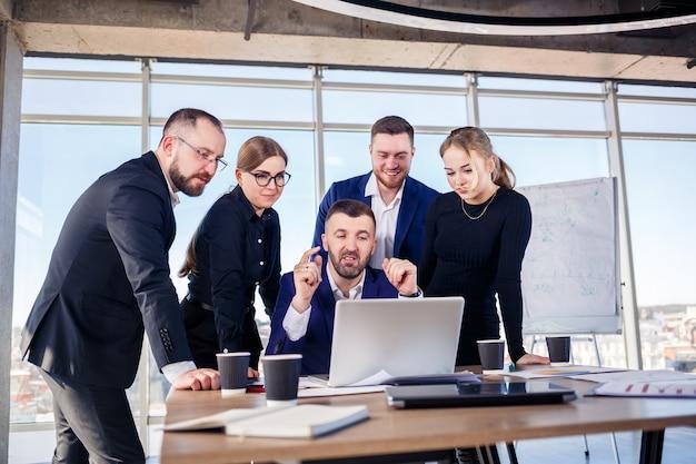 Счастливые деловые люди, глядя на презентацию ноутбука, успех на работе, сидя в современном офисе. успешные онлайн-переговоры. бизнесмены делятся своими знаниями