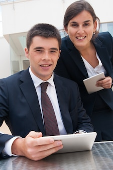 Happy business people posing at camera and holding tablets