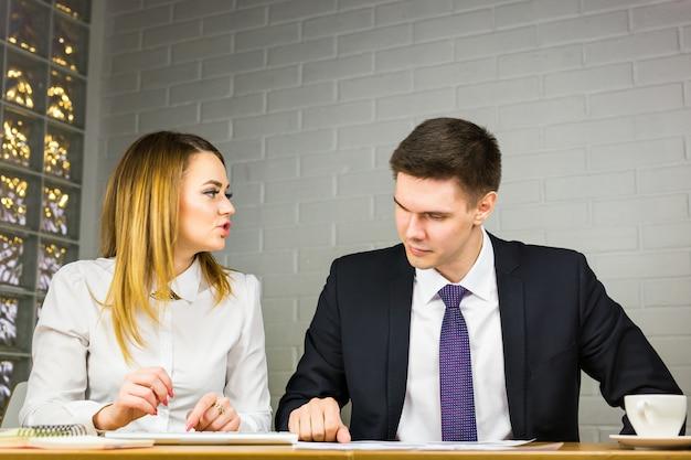 Счастливые деловые люди говорят на встрече в офисе.