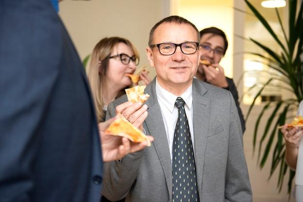 Команда счастливых деловых людей ест пиццу в офисе на обеденный перерыв