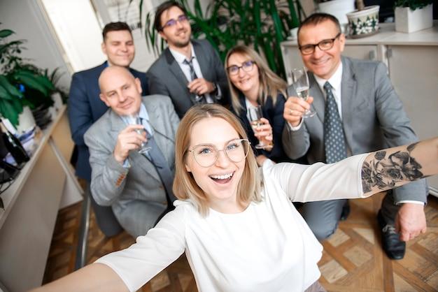 Счастливая команда деловых людей с бокалами шампанского, делающими селфи на деловой встрече