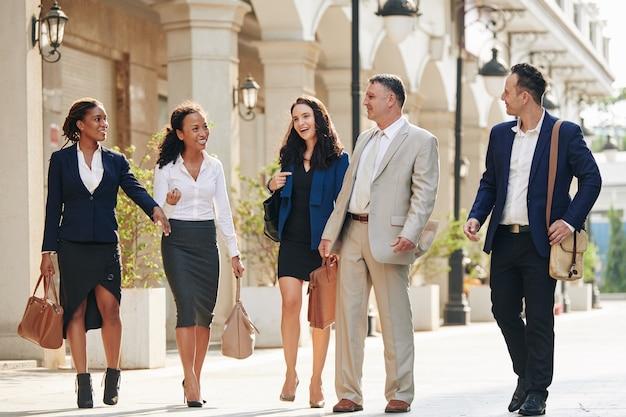 Счастливые деловые люди, идущие по улице