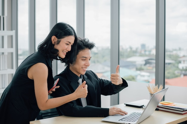 Счастливые деловые люди с большими пальцами руки вверх на видеозвонке с ноутбуком в офисе