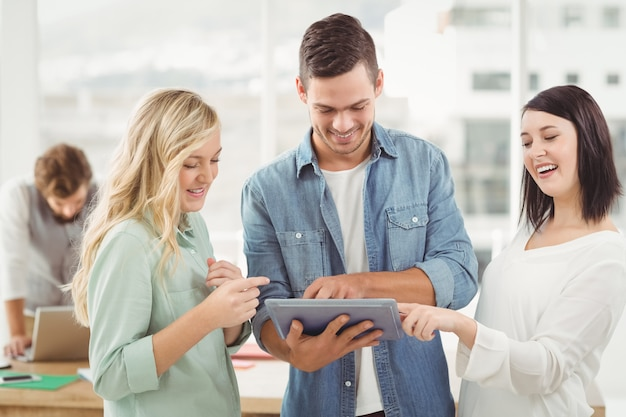 Happy business professionals using digital tablet at office