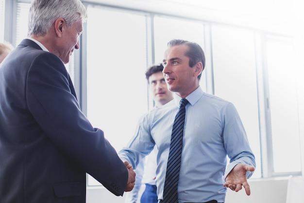 Счастливый бизнес, пожимая руки в современном офисе
