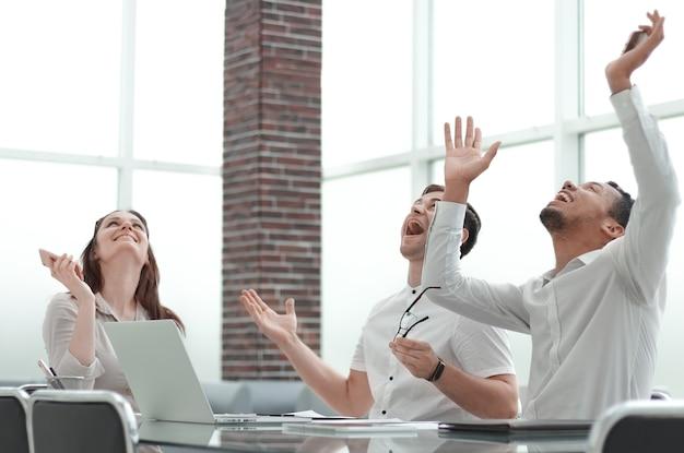 Счастливая бизнес-команда празднует успехи в бизнесе в ярком офисе. фото с копией пространства