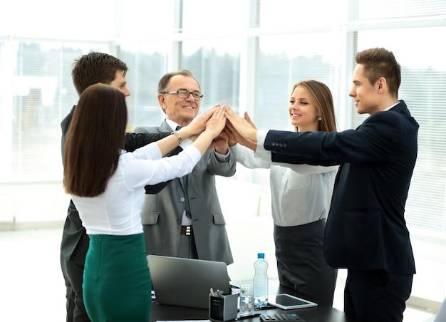 Счастливая бизнес-команда празднует победу в офисе