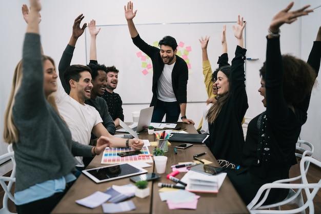 사무실에서 제기 손으로 축하 행복 비즈니스 팀. 성공과 승리의 개념.