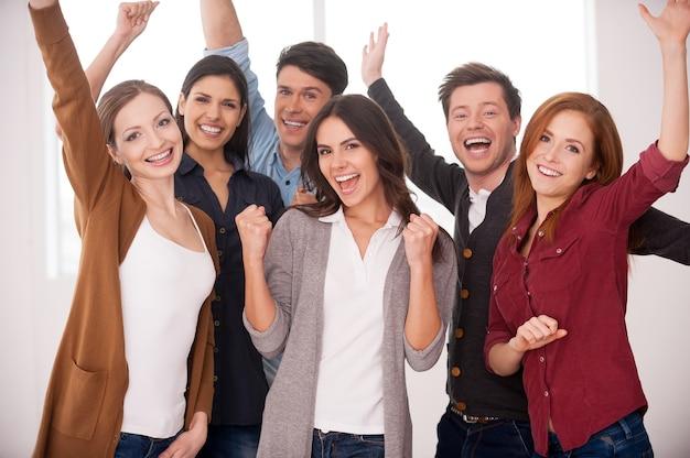 Счастливая бизнес-команда. группа веселых молодых людей, стоящих рядом и с поднятыми руками