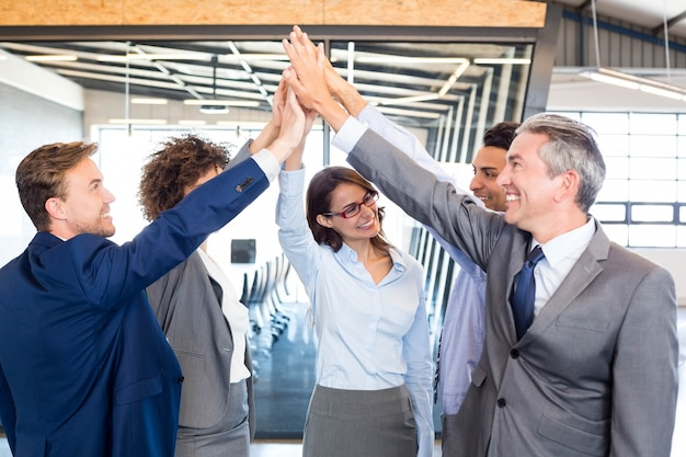 Happy business  team high fiving in office