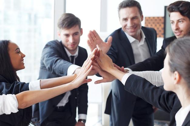 Счастливая бизнес-команда делает пять руками в офисе