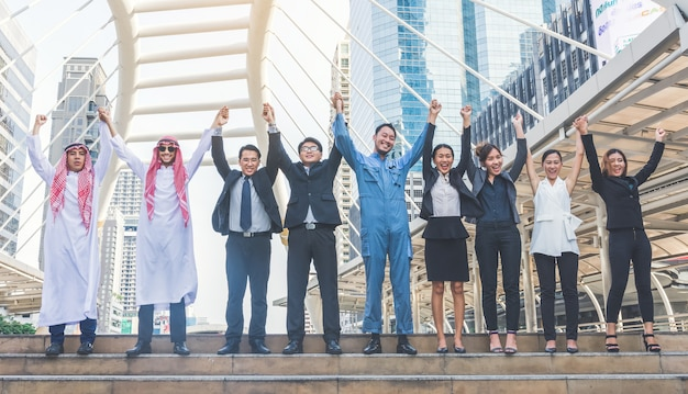 Happy business team making high hands in city background