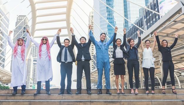 도시 배경에서 높은 손을 만드는 행복 비즈니스 팀