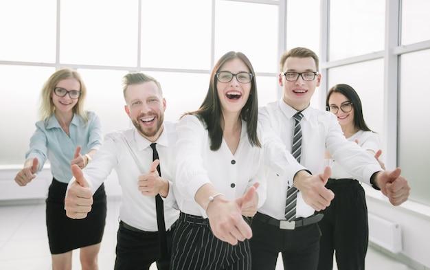 親指を立てて幸せなビジネスチーム。成功の概念