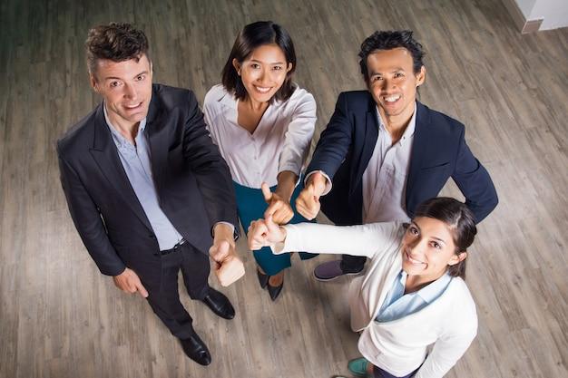 Squadra felice di affari mostra pollice in alto nel padiglione