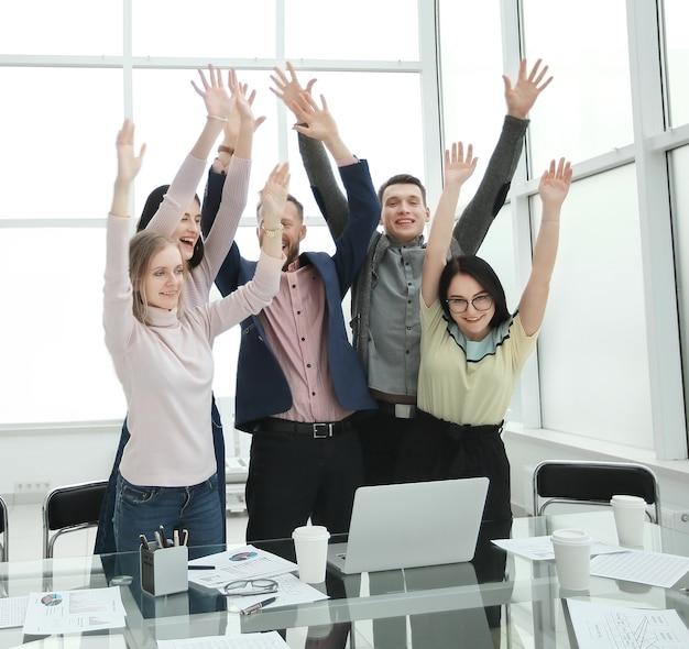 Счастливая бизнес-команда, стоящая возле рабочего стола с поднятыми руками