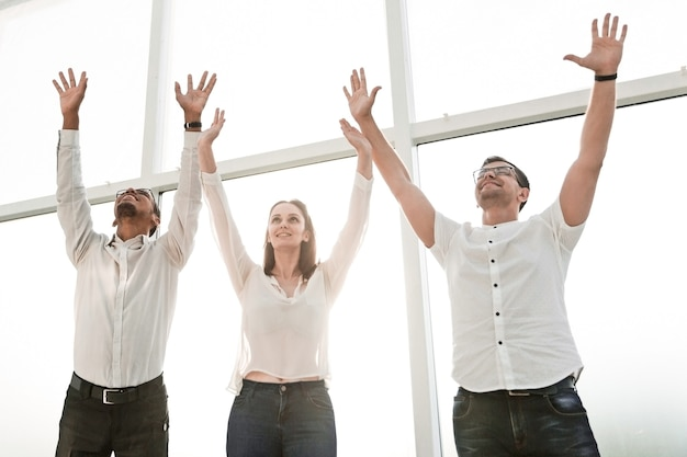 Happy business team standing together and lifting their hands up