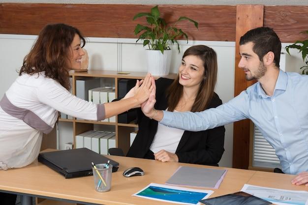 Счастливая команда бизнес с беременной женщиной, давая высокие пять в офисе