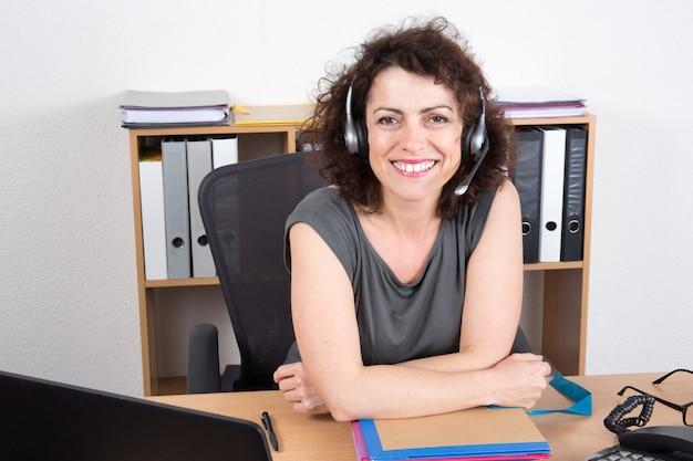 Счастливый деловая женщина в офисе, улыбаясь в колл-центр