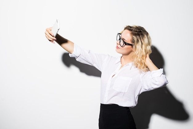 Happy business woman in eyeglasses taking selfie photo smartphone isolated on white wall